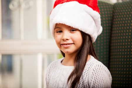 Portrait of a beautiful little girl wearing Santa s hat at home Stock Photo - 22568635