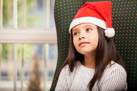 Beautiful little girl in Santa s hat daydreaming and looking up towards copy space Stock Photo - 22568636