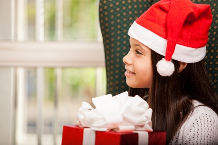 Cute little Hispanic girl in Santa s hat holding a gift and looking towards copy space Stock Photo - 22568637
