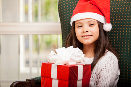 Excited little girl holding a Christmas gift and wearing Santa s hat Stock Photo - 22568638