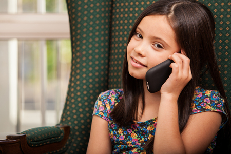 phone: Pretty little Hispanic girl talking on a cell phone with her mom