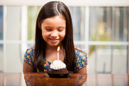 Happy little girl making a wish and celebrating her birthday with a cupcake Stock Photo - 22568644