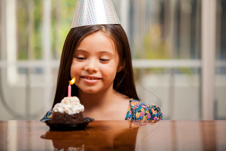 Beautiful little girl on a party hat making a birthday wish on her birthday Stock Photo - 22568645