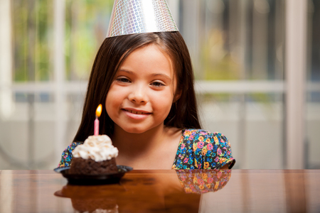 Happy little Hispanic girl celebrating her birthday with a party hat and a cupcake Stock Photo - 22568646