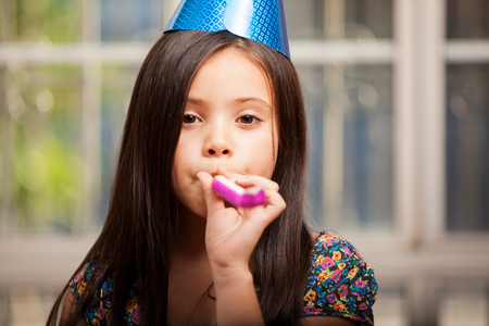 noisemaker: Cute little girl celebrating her birthday with a party hat and a noisemaker