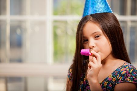 birthday party kids: Happy little girl with a noisemaker and a party hat, celebrating her birthday