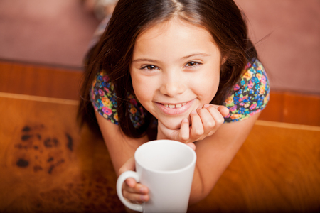 Beautiful little Latin girl drinking a cup of tea and smiling photo