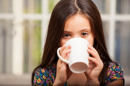 Pretty little girl drinking hot chocolate and relaxing at home photo