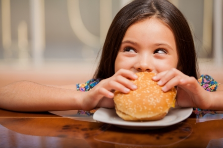 hungry children: Cute little Latin girl eating a hamburger and looking up towards copy space