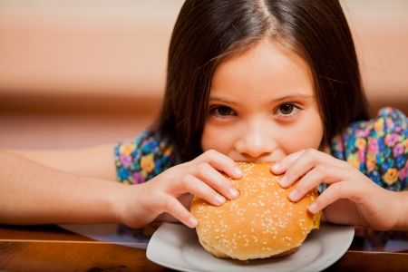latin food: Portrait of a little girl biting a cheeseburger at home Stock Photo