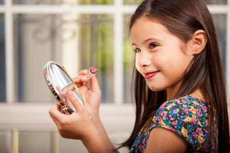 Cute happy girl looking at herself in a mirror while putting on some lipstick Stock Photo - 22568686