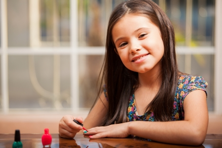 polish: Little Latin brunette trying some nail polish on her nails and smiling