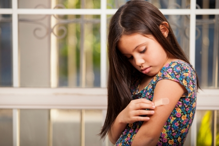 arm: Cute little acting all sad and girl putting a band-aid on her arm Stock Photo