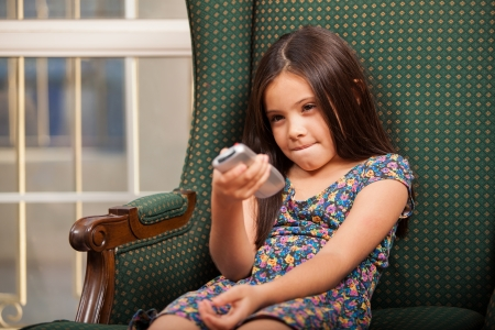 Beautiful little girl relaxing on a chair in the living room and holding a TV remote photo