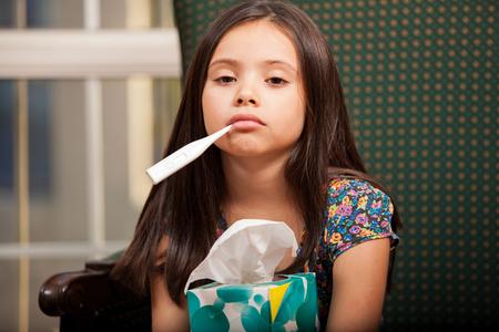 ni�os enfermos: La ni�a sufre de un resfriado, sosteniendo una caja de pa�uelos y un term�metro en la boca
