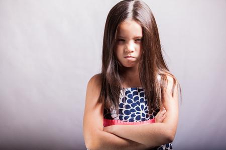 Portret van een kleine brunette met de armen gekruist en handelen allemaal gek op een witte achtergrond