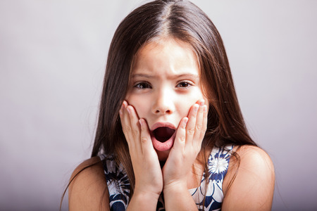Portrait of a Hispanic little girl with her mouth open and hands on her face, acting all surprised on a white background photo