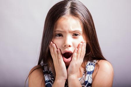 boca abierta: Retrato de una niña hispana con la boca abierta y las manos en la cara, actuando absoluto sorprendido en un fondo blanco Foto de archivo