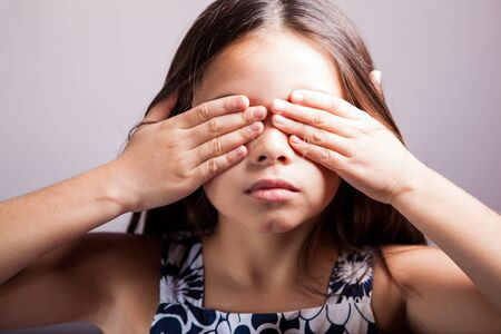 censorship: Little brunette covering her eyes with her hands on a white background
