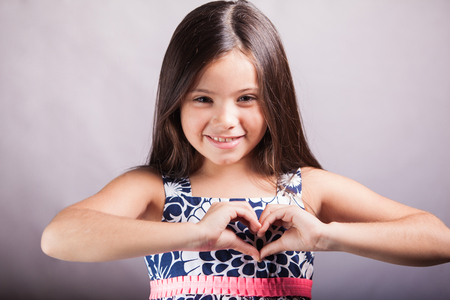 Cute little girl in a dress making a heart with her hands and smiling on a white background photo