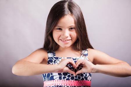 forme: Petite fille mignonne dans une robe faisant un coeur avec ses mains et souriant sur un fond blanc