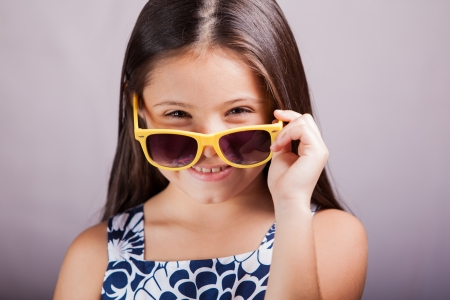 kids dress: Beautiful little Hispanic brunette wearing sunglasses and a cute dress on a white background