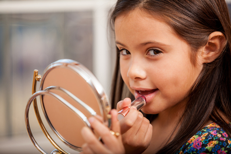 Cute little girl trying on her mom s lipstick and smiling Stock Photo - 22568561