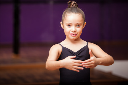 Portrait of a cute little girl practicing a dance pose in a dance academy photo