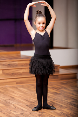 a rehearsal: Beautiful little ballerina wearing tights and a skirt practicing a ballet pose in dance class
