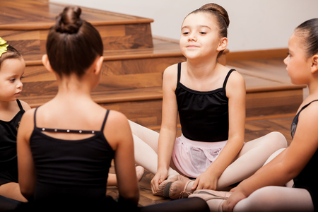 Pretty little Latin girls warming up and stretching for their dance class photo