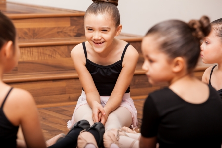 Happy little girl having fun with her friends during dance class in a dance academy photo
