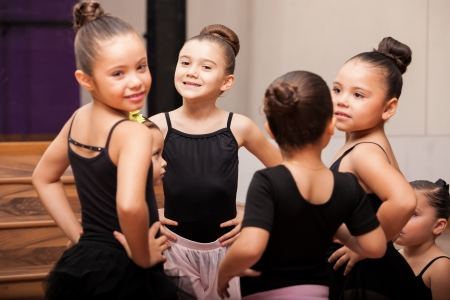 ballet niñas: Niñas hermosas vistiendo medias y faldas que se divierten en una clase de ballet y sonriente Foto de archivo