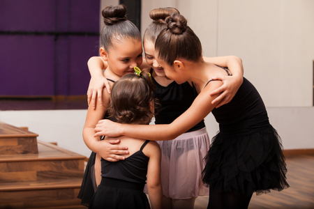 friend hug: Pretty little Hispanic friends having fun during a ballet class in a dance academy