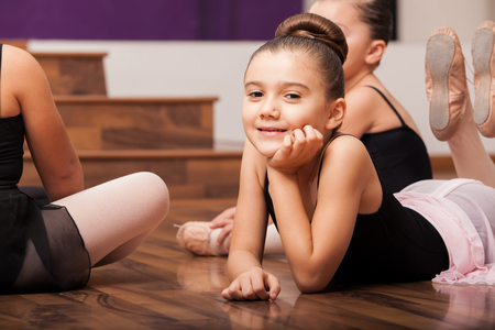 Beautiful little dance student laying on the floor and taking a break in dance class photo