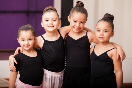 ballet dancing: Pretty little girls having fun and hugging each other during a dance class