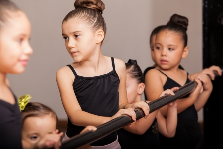 Cute little ballet dancers standing next to a ballet barre and paying attention to their teacher photo