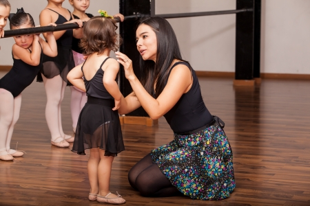 or instruction: Young female dance instructor comforting one of her younger ballet students during a dance class
