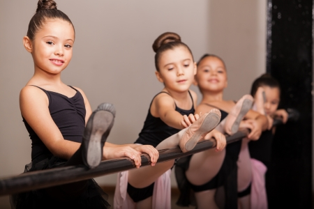 Cute little girl loving her ballet class and raising her leg on a ballet barre