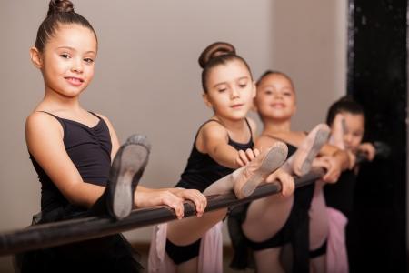 Schattig klein meisje liefdevolle haar balletles en de opvoeding van haar been op een ballet barre