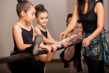 dance teacher: Beautiful little ballet dancers listening to her teacher s directions while raising their legs on a barre Stock Photo