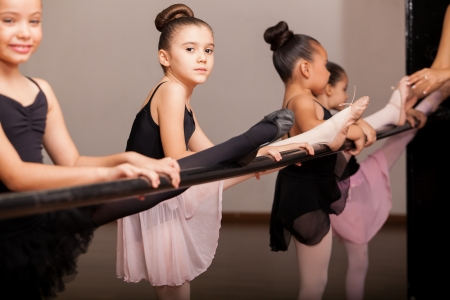 Schattige kleine balletdansers beoefenen enkele danspasjes in een barre in een dansles