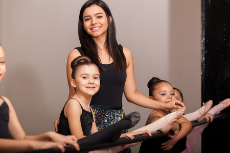 barre: Beautiful young dance instructor coaching her female students in a dance academy