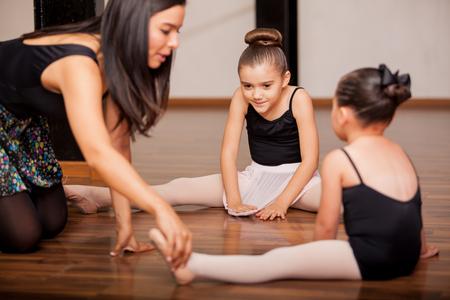 ballet: Ni�as Pretty hispana escuchar sus instrucciones instructor de baile durante una clase de danza Foto de archivo