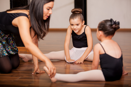 ballerina tights: Pretty Hispanic little girls listening to her dance instructor directions during a dance class Stock Photo