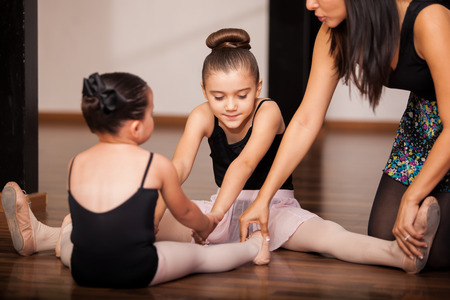 Two little girls warming up and getting instructions by their dance instructor in a dance academy