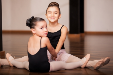 ballerina tights: Cute little girls having fun and holding hands while doing some stretching exercises during a ballet class Stock Photo