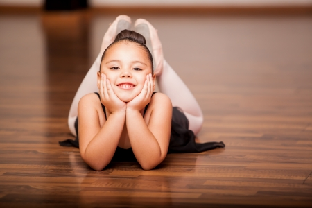 Portrait of a cute and happy little girl taking a break during a ballet class photo