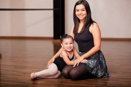 Cute female dance instructor and a student having fun and smiling during dance class