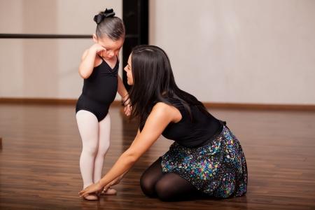 Vrouwelijke dans instructeur probeert een van haar kleine studenten troosten tijdens een balletles