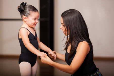 cute little girl smiling: Beautiful female dance instructor talking to and coaching one of her students in a dance academy